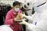 <b>배식 받는 우한 임시병원의 코로나19 환자들</b><br>중국 후베이성 우한의 대형 컨벤션 센터를 개조한 임시병원에서 지난 15일 신종 코로나바이러스 감염증(코로나19) 환자들이 방호복을 착용한 의료진으로부터 점심 배식을 받고 있다. 우한/로이터 연합뉴스