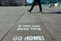 <b>베를린 광장에 등장한 코로나19 '집으로 가라' 그라피티</b><br> 독일이 신종 코로나바이러스 감염증(코로나19) 확산 방지를 위해 공공장소에서 '2인 초과 접촉 제한령'을 내린 이후 24일(현지시간) 한 시민이 베를린의 텅 빈 알렉산더플라츠 광장에 적힌 '이걸 읽을 수 있으면 집으로 가라'는 내용의 그라피티 옆을 걸어가고 있다. 베를린/로이터 연합뉴스