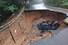 8일 오전 전남 장성군 못재 인근 도로가 폭우로 무너지면서 트럭 한대가 뒤집혀 있다. 광주전남 지역은 이틀간 내린 기록적인 폭우로 도로가 잠기고 산사태로 인명 피해가 발생하는 등 비 피해가 속출하고 있다.연합뉴스