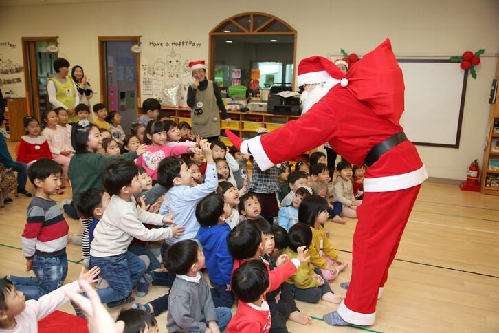 <b>산타와 하이파이브</b><br>24일 경북 포항시청어린이집에서 산타클로스와 루돌프 복장을 한 사람이 어린이들에게 선물을 나눠주고 있다. 포항/연합뉴스