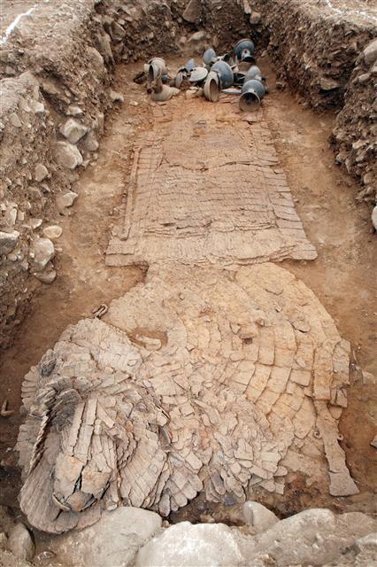 2009년 조사 중 발견된 쪽샘 C10호 고분의 마갑 출토 모습. 아랫부분 말의 목 부분 가리개이고 뒤쪽의 네모진 부분이 몸통이다. 펼쳐진 말 갑옷 위에 장수의 찰갑이 얹혀진 채로 발견됐다.