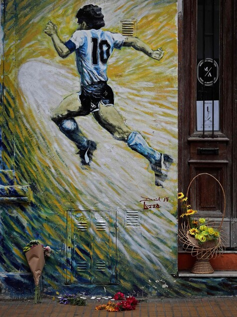 디에고 마라도나 사망 당일인 11월25일(현지시각) 아르헨티나 부에노스아이레스 산텔모 인근에 그려진 그의 벽화 앞에 추모의 꽃들이 놓여 있다. 부에노스아이레스/AFP 연합뉴스