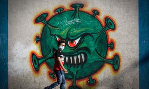 코로나 바이러스 벽화 앞 팔레스타인 소년