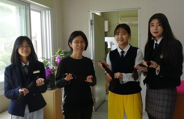 목포항도여중 최민아 학생(왼쪽부터), 방주현 교사,  부예선·박신혜 학생이 소아암 환자들을 돕기 위해 기부한 머리카락을 들고 있다. 사진 목포항도여중