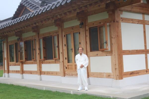 오대산 자연명상마을의 조정래문학관 '세심헌'은 전통 한옥으로 지어졌다. 조정래 작가가 지난 25일 한복 차림으로 처마 밑에서 비를 피하고 있다. 사진 최재봉 선임기자