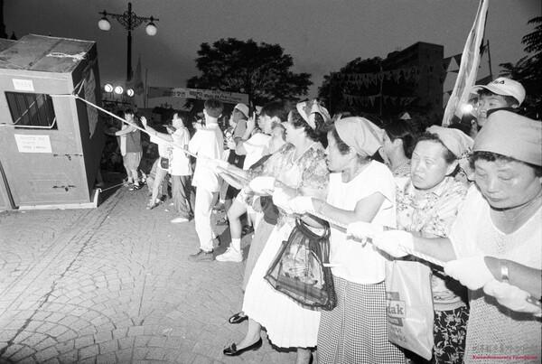 임기란(맨오른쪽) 어머니가 1995년 8월8일 민가협 어머니들이 양심수 석방을 요구하며 명동성당 입구에 세워둔 모형 감옥을 부수고 있다. 기록사진가 박용수씨가 찍었다.