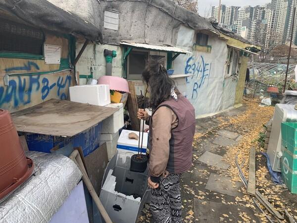서울 강남구에 있는 쪽방촌 구룡마을 주민 이아무개씨가 집게로 연탄을 집어들고 있다. 김윤주 기자