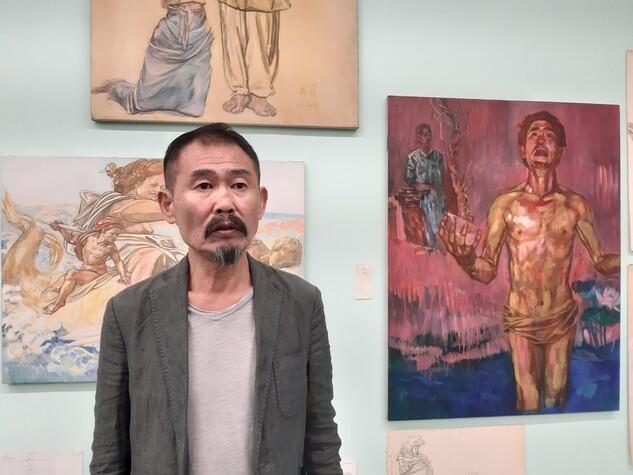 아카이브처럼 꾸며진 지하 전시장에서 작품에 대해 말하고 있는 최민화 작가. 오른쪽에 있는 알몸 남자의 그림은 그의 자화상이다.