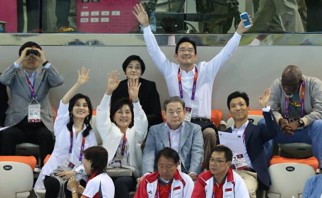 이건희 삼성전자 회장 가족들이 2012년 7월 영국 런던 올림픽파크의 아쿠아틱스 센터에서 열린 2012 런던올림픽 남자 자유형 400m 결승을 참관하기 위해 수영장을 찾아 건너편에 있는 지인과 인사하고 있다. 올림픽사진공동취재단