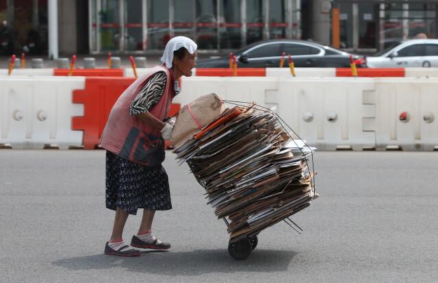 2016년 8월 서울 서부역 도로를 한 할머니가 한낮의 땡볕을 손수건 한장으로 겨우 가린 채 폐지를 고물상으로 가지고 가고 있다. 김봉규 선임기자 bong9@hani.co.kr