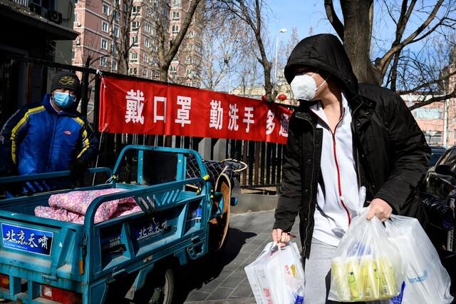 지난 1일 중국 수도 베이징에서 양손에 물건을 든 남성이 마스크를 눌러 쓴 채 거리를 지나고 있다. AFP 연합뉴스