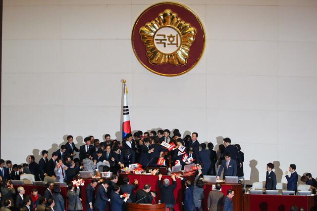 '공직선거법' 개정안 투표가 예정된 12월27일 국회 본회의장의 문희상 국회의장석을 둘러싸고 여야 의원들이 심한 몸싸움을 벌이고 있다. 연합뉴스