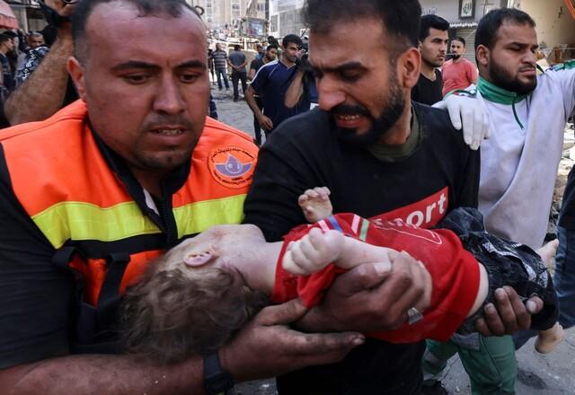 16일 팔레스타인 가자지구에서 구조대가 이스라엘 공습으로 파괴된 건물에서 발견한 아이의 주검을 옮기고 있다. 가자/AFP 연합뉴스
