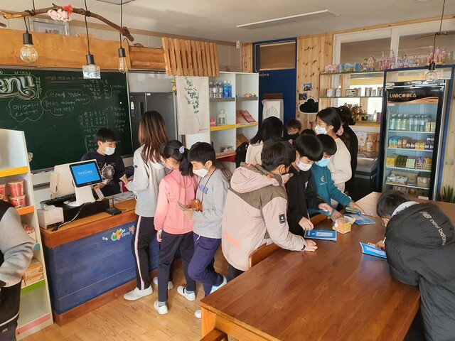 매주 2천원의 매점 화폐를 지급받는 충북 판동초등학교 어린이들에게 기본소득은 생활의 한 부분이다. 매점에서 기본소득의 사용 내용을 기록하는 아이들. 강환욱 교사 제공