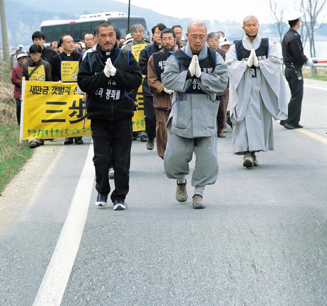 2003년 수경 스님(오른쪽)과 문규현 신부(왼쪽)가 새만금 생명 파괴를 반대하며 전북 부안에서 서울까지 삼보일배 행진을 이끌고 있다. <한겨레> 자료 사진