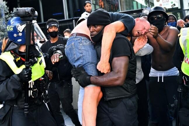 13일(현지시각) 인종차별 시위 과정에서 위기에 처한 백인 브린 메일(55)이 흑인 트레이너 패트릭 허친슨에 의해 구조되고 있다. 런던/로이터 연합뉴스