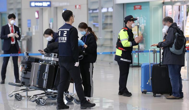 영국 런던발 항공편으로 입국한 외국인들이 24일 오후 인천국제공항 2터미널에 도착해 임시생활시설로 향하는 버스를 타기 위해 이동하기 전 경찰과 육군 현장 지원팀의 설명을 듣고 있다.연합뉴스