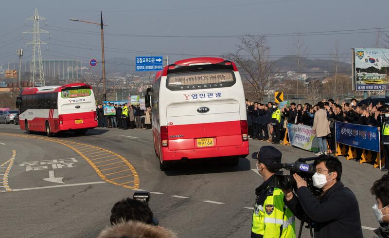 코로나19로 아산 임시생활시설에 격리됐던 우한교민 193명을 태운 버스가 15일 오전 아산시민들의 환송을 받으며 충남 아산시 초사동 경찰인재개발원을 떠나고 있다. 연합뉴스