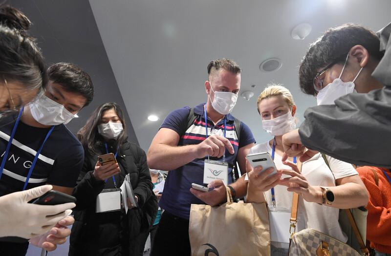 중앙사고수습본부가 홍콩과 마카오에서 입국하는 여행객에 대해서도 전수 검역조처를 결정한 가운데 13일 인천국제공항을 통해 홍콩에서 입국하는 사람들이 관계자의 설명을 들으며 스마트폰에 자가진단 애플리케이션을 설치하고 있다. 인천공항/공항사진기자단