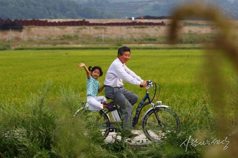 손 흔드는 손녀 서은 양을 자전거에 태우고 봉하벌판을 달리는 노무현 전 대통령. 노무현 사료관 제공