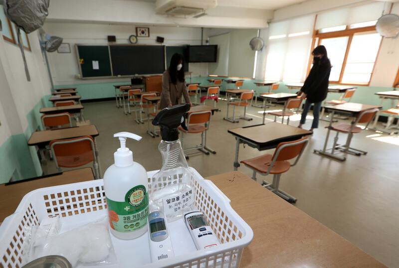 24일 광주 동구의 한 고등학교에서 선생님들이 체온계와 손 소독제 등을 비치한 교실에서 책상의 간격을 벌리고 있다. 연합뉴스