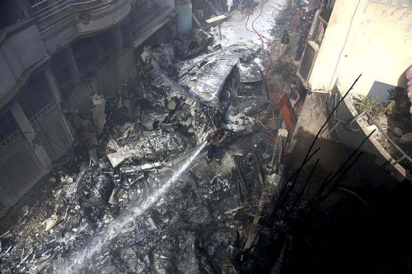 승객 등 100여명이 탑승한 파키스탄 항공기가 22일(현지시각) 오후 카라치 인근 한 마을에 추락했다. 한 소방요원이 항공기 잔해에 물을 뿌리고 있다. AP 연합뉴스