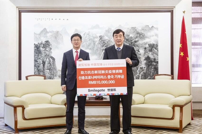 양동기(왼쪽) 스마일게이트 대외담당 사장이 5일 주한 중국대사관에서 싱하이밍 주한 중국대사에게 1000만원 위안의 성금을 전달하고 있다. 스마일게이트 제공