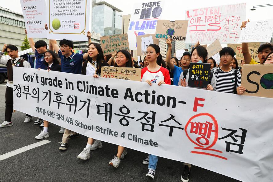 지난해 9월27일 '기후를 위한 결석 시위'에 참여한 청소년들이 '정부의 기후위기 대응점수 빵점'이라 쓰인 펼침막을 들고 서울 광화문 거리를 행진하고 있다. 앞줄 빨간색 옷을 입은 이가 김도현(17)양이다. 청소년기후행동 제공