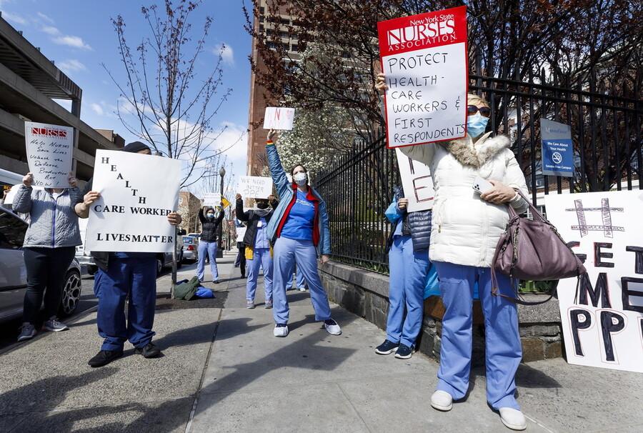 """지난 2일 미국 뉴욕 브롱크스의 한 병원 앞에서 간호사노조 소속 간호사들이 """"보건 종사자와 응급 의료인들을 보호하러""""고 쓴 손팻말을 든 의료용 보호장구 확보를 촉구하는 시위를 벌이고 있다. 뉴욕/EPA 연합뉴스"""