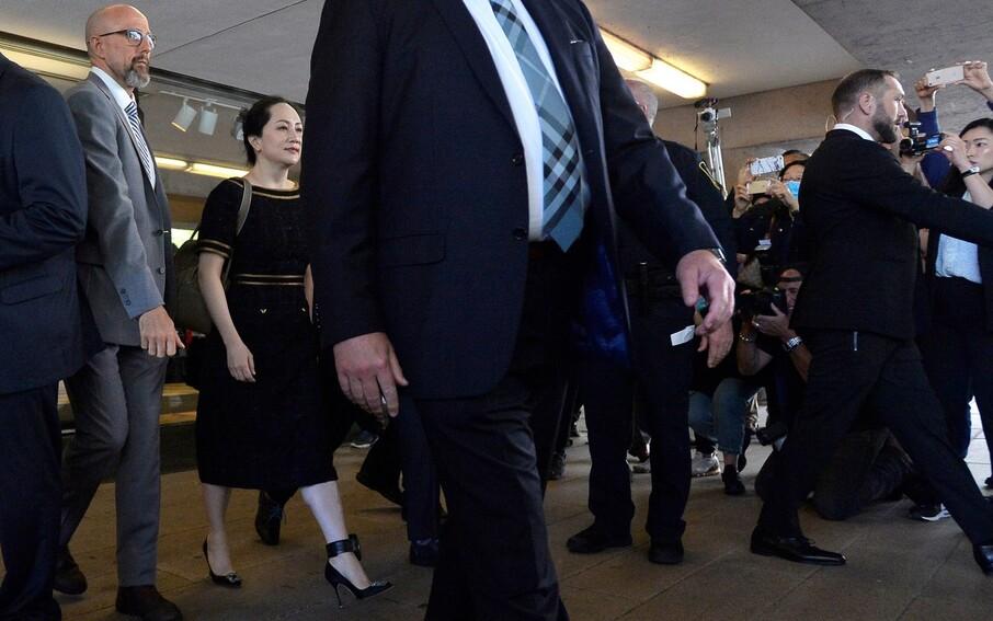 멍완저우 화웨이 부회장(왼쪽 둘째)이 27일 캐나다 밴쿠버에 있는 브리티시콜롬비아주 대법원의 재판을 받은 뒤 나오고 있다. 그의 왼쪽 발목에 위치추적기가 달려 있다. 밴쿠버/로이터 연합뉴스