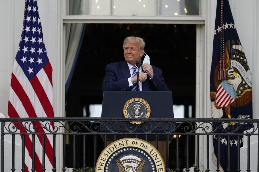 도널드 트럼프 미국 대통령이 10일 워싱턴 백악관 블루룸의 발코니에서 유세하면서 마스크를 벗고 있다. 워싱턴/AP 연합뉴스