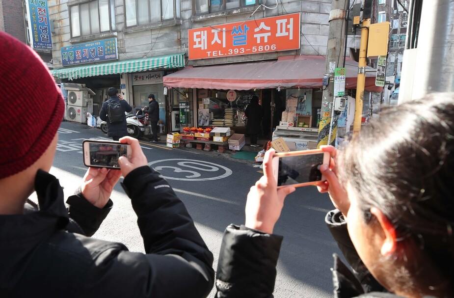 영화 <기생충>이 제92회 아카데미 시상식에서 작품상을 포함한 4관왕을 차지한 가운데 11일 오전 서울 마포구 <기생충> 촬영현장이었던 '돼지쌀슈퍼' 일대에서 미국인 관광객들이 기념사진을 찍고 있다. 백소아 기자 thanks@hani.co.kr