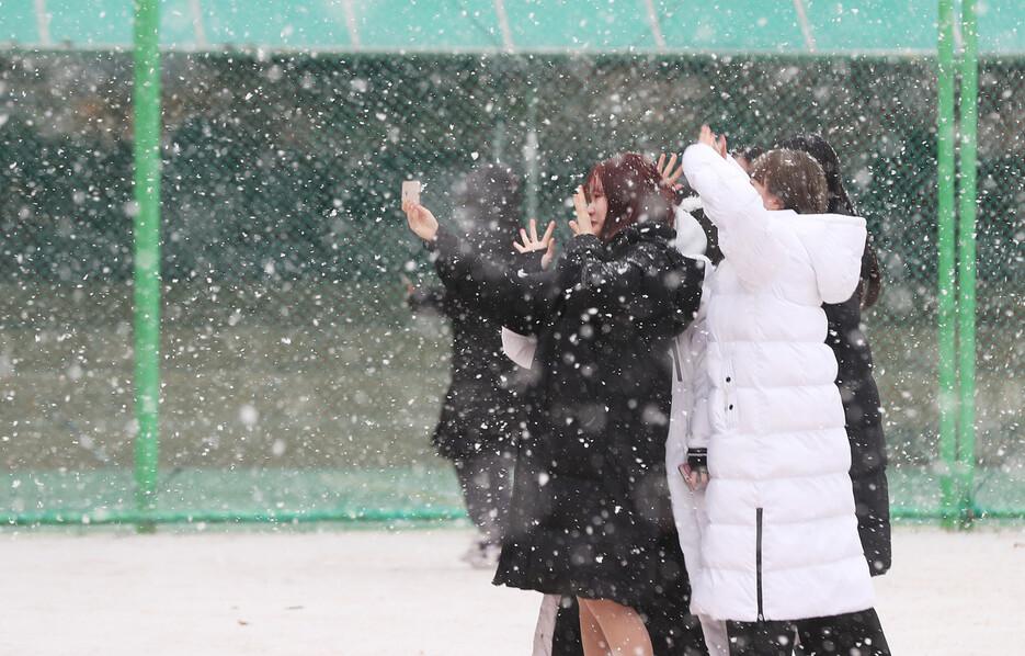 한 무리의 학생들이 지난해 12월 내리는 눈을 맞으며 사진을 찍고 있다. 연합뉴스