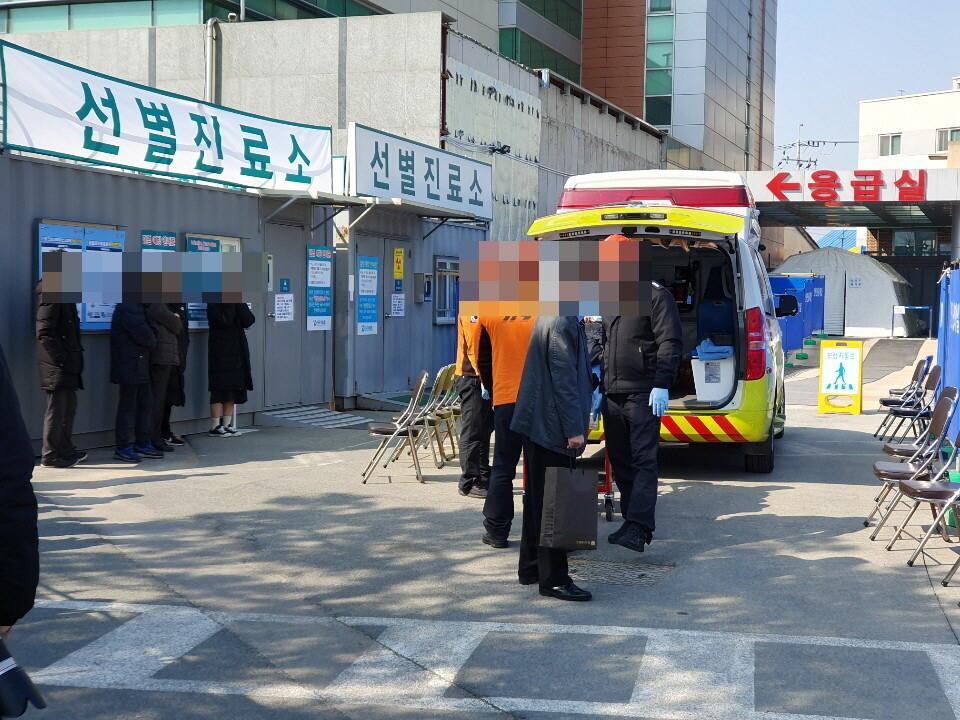 지난 20일 119구급대원이 대구의료원 선별진료소에 코로나19 의심 환자를 옮기고 있다.
