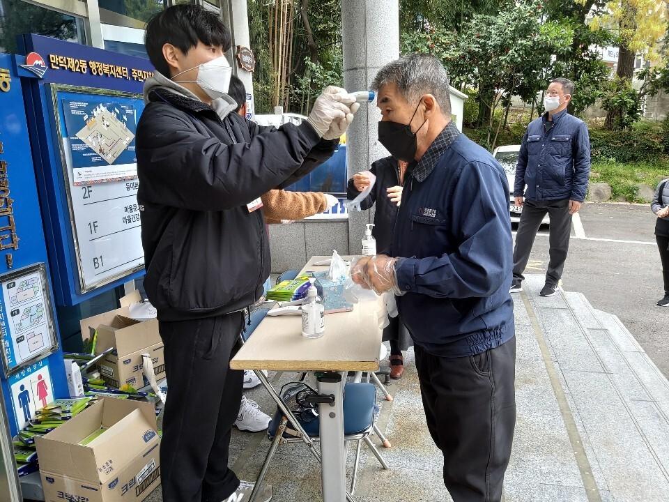 부산 북구 만덕2동주민센터 앞에서 일회용 위생장갑을 받아든 유권자가 발열 검사를 받고 있다. 김광수 기자