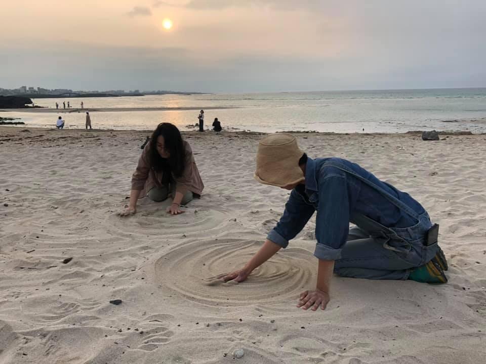 모래 속에 숨은 플라스틱 조각들을 찾기 위해 절을 하듯 몸을 낮춰 끊임없이 모래를 쓰다듬는 '플라스틱 만다라' 참가자들. 에코오롯 제공
