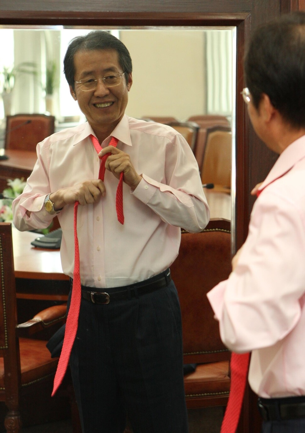 이 사진이 내 눈길을 끈다. 언제나 이를 악물 것 같은 홍준표가 거울 앞에서 편하게 웃는다. 2008년에 강창광 기자가 찍었다. 이때도 빨간 넥타이를 좋아했다. 홍준표는 대선이 있는 2022년에 다시 웃을 수 있을까?