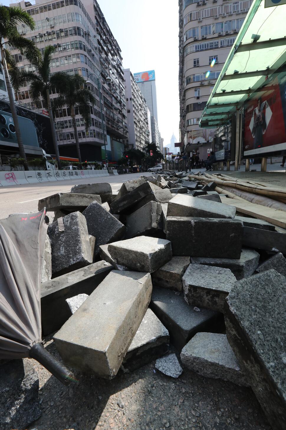 지난 24일 오후 홍콩 침사추이 중심 도로에 경찰의 기습 체포 작전을 저지하기 위해 사용했던 벽돌이 한쪽에 쌓여 있다.