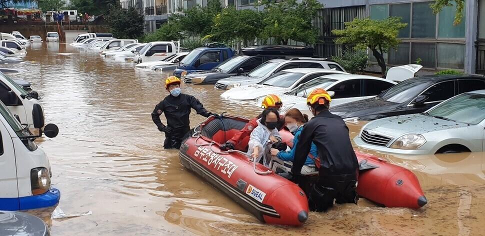 지난 30일 오전 대전의 한 아파트 주차장과 건물 일부가 물에 잠겨 주민들이 소방대원의 도움을 받아 구명정을 타고 아파트에서 빠져나오고 있다. 대전/박종식 기자 anaki@hani.co.kr