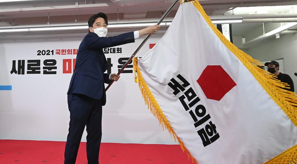 11일 서울 여의도 국민의힘 당사에서 열린 전당대회에서 새로 선출된 이준석 대표가 당기를 흔들고 있다. 공동취재사진