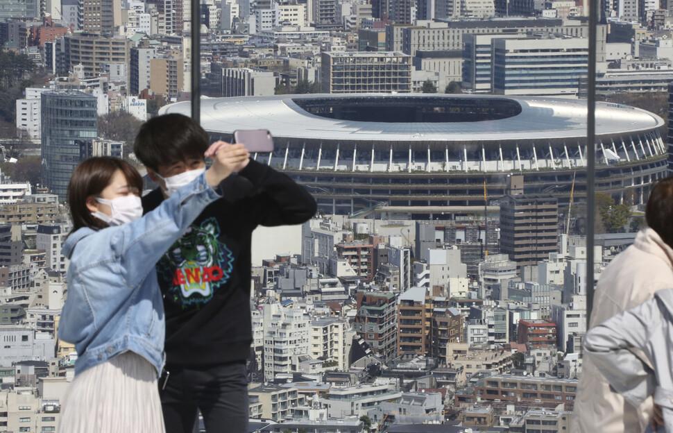 25일 도쿄올림픽 주경기장으로 쓰일 예정인 일본 도쿄 국립경기장을 배경으로 마스크를 쓴 이들이 사진을 찍고 있다. 도쿄/AP 연합뉴스