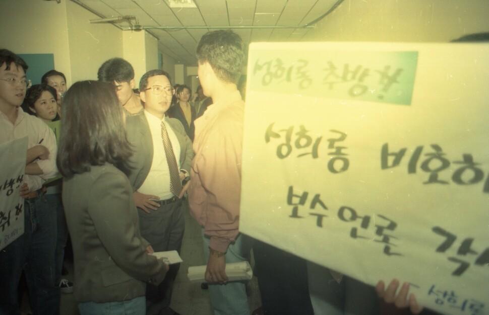 피해자의 연대자로 보이는 사람들이 '성희롱 추방! 성희롱 비호하는 보수언론 각성하라!'라는 피켓을 들고 누군가에게 항의하고 있다.