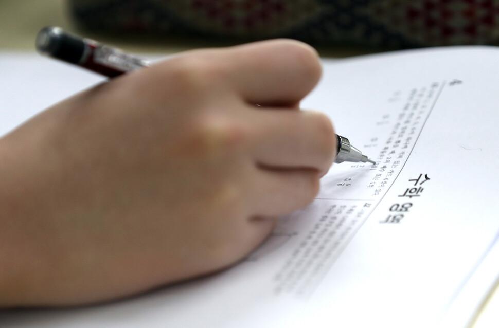 고등학교 전국연합 학력평가가 실시된 3월23일 서울 시내 한 고등학교에서 학생들이 시험 전 기출문제 등을 보고 있다. 연합뉴스