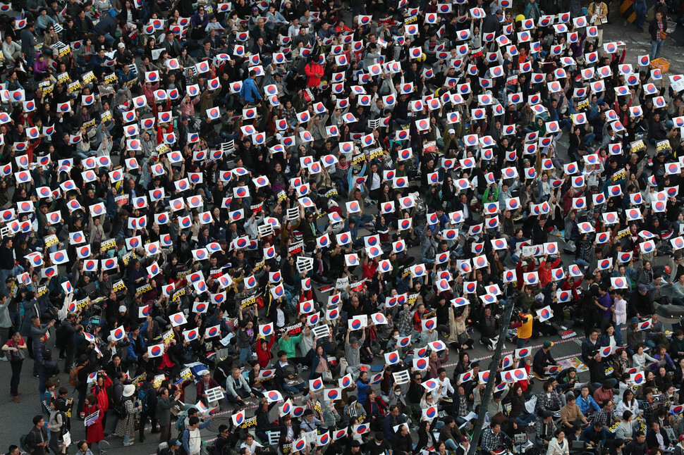 '제10차 사법적폐 청산을 위한 검찰 개혁 촛불 문화제' 참가자들이 19일 오후 서울 여의도 국회의사당 앞에서 태극기 손팻말을 든 채 검찰개혁 법안의 국회 통과를 촉구하고 있다. 김정효 기자