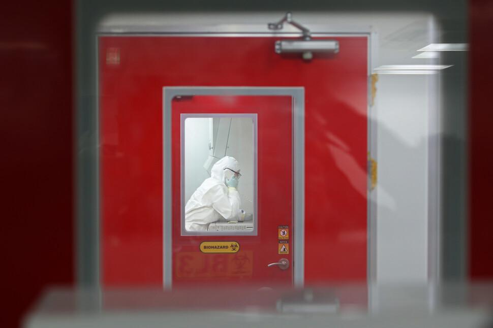25일 오후 광주 서구 화정동 광주시보건환경연구원 생물안전밀폐실험실에서 직원이 이중 문이 달린 격리 공간 안쪽에서 인터폰으로 동료와 대화하고 있다. 연합뉴스