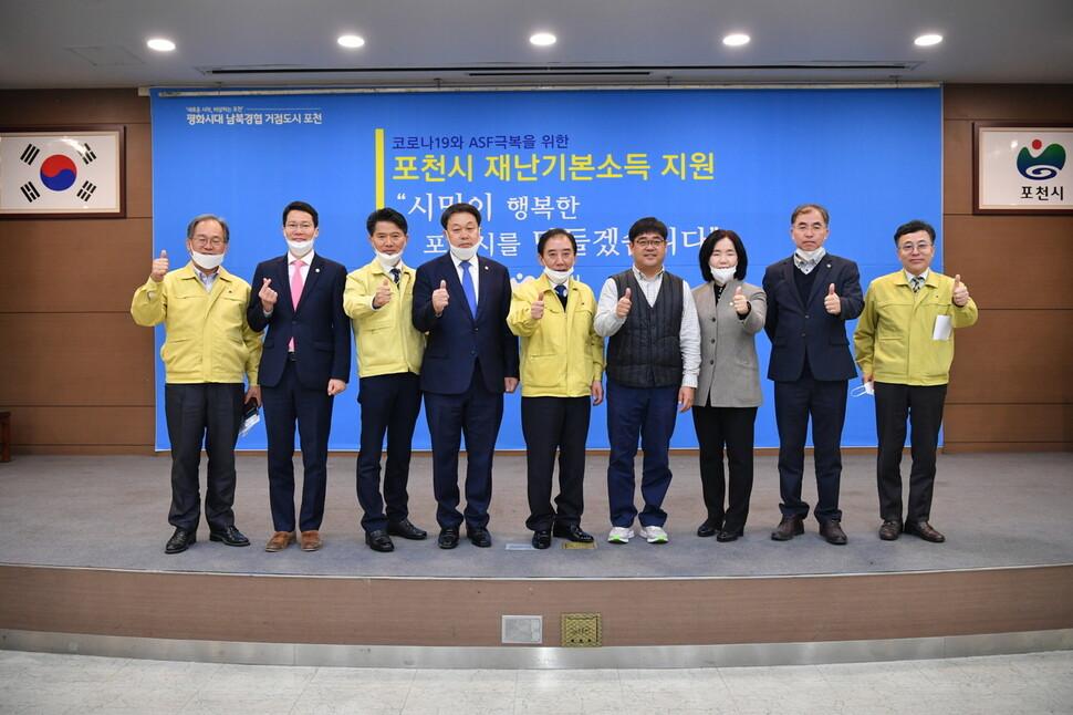 박윤국 포천시장(가운데)과 포천시의회 의원 등이 31일 오전 시청 대회의실에서 '1인당 40만원 재난기본소득 지급' 관련 기자회견을 연 뒤 기념 촬영을 하고 있다.