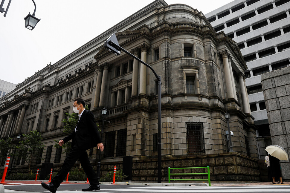 임시 금융정책회의가 열린 22일 일본 도쿄 일본은행 앞에서 한 남성이 마스크를 쓰고 걸어가고 있다. 도쿄/로이터 연합뉴스