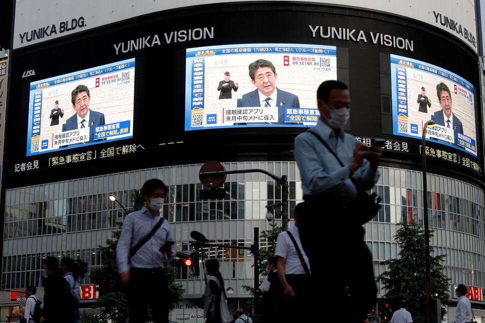 25일 일본 도쿄 신주쿠의 한 대형 전광판에 아베 신조 총리의 코로나19 긴급사태 해제 관련 기자회견 방송이 비치고 있다. 도쿄/로이터 연합뉴스