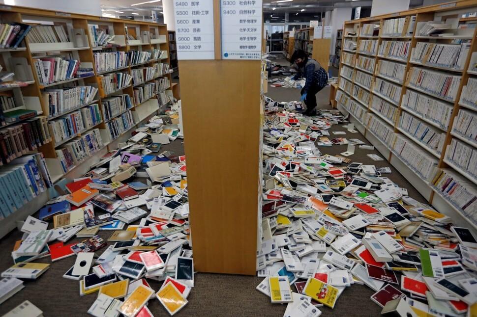 14일(현지시각) 일본 후쿠시마현 이와키시의 이와키시립도서관에서 직원이 후쿠시마 지진의 영향으로 책꽂이에서 떨어진 책들을 정리하고 있다. 로이터 연합뉴스