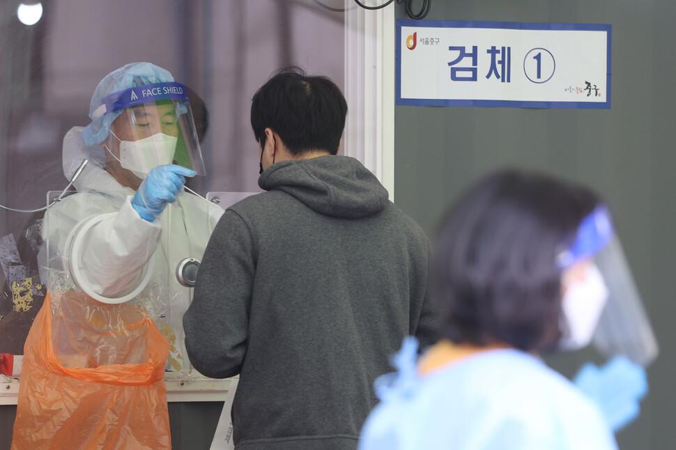 17일 오전 서울역광장에 마련된 임시선별진료소에서 의료진이 검체 채취를 하고 있다. 연합뉴스